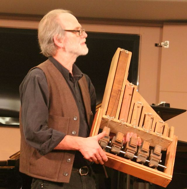 Trimpin holding a prototype for Nancarrow's aborted percussion orchestra experiment's